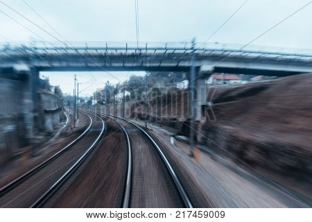 View from the last coach of high-speed suburban train: railway tracks turning to the left under the bridge houses poles with wires and dull evening sky; strong motion blur