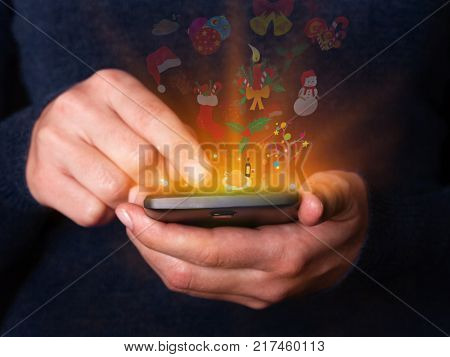 Woman hands holding and using smartphone mobile or cell phone for Christmas or xmas. Concept for celebration with logos of  Santa Claus hat, a holy berry, a snowman, a gingerbread, a candle and bells