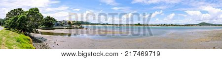 Panorama of Ngunguru Harbour river estuary at low tide - waterfront with anchored motor boat near mud flats in Northland New Zealand NZ