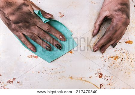 Low-paid job and low-skilled professions. Dirty woman hands cleaning surface with a towel