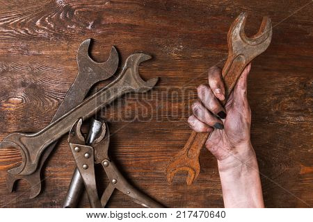 Female repairer. Woman hand holding a spanner and other tools lay on a wooden background. Feminism and emancipation concept poster