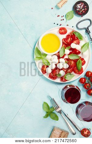 Italian antipasti snack for wine. Mozzarella cheese, fresh basil leaves, tomatoes, olive oil and glasses of red wine on concrete background, top view. Caprese salat