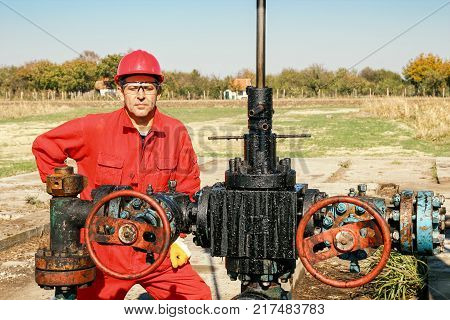 Worker at Oil Well.  Portrait of a worker beside pump jack oil well.
