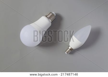 A comparative large and small light bulb small and medium business. Lamps are on a gray background