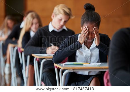 Anxious Teenage Student Sitting Examination In School Hall poster