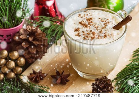 Eggnog traditional drink for Christmas celebration in glass topped with ground nutmeg and cinnamon stick. Homemade eggnog in top view with copy space in Christmas theme and snowfall effect background. Delicious eggnog for Christmas party.