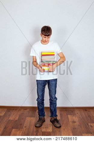 Sad Student with the Books on the White Wall Background