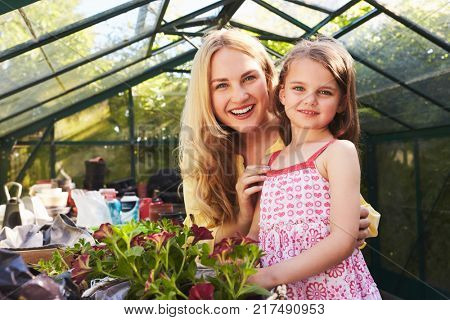 Portrait Of Mother And Daughter Planting Basket In Greenhouse