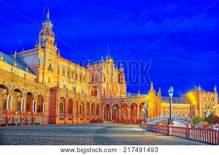 Spain Square (Plaza de Espana)is a square in the Maria Luisa Park in Seville Spain built in 1928 for the Ibero-American Exposition of 1929. Nighttime. poster