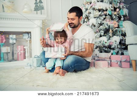 Dad and daughter are sitting and opening a Christmas present near the Christmas tree. Happy New Year.