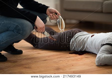 murder and robbery concept - criminal or murderer holding knife in blood and jewelry and dead woman body lying on floor at crime scene (staged photo)