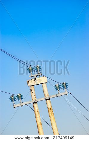 Electric power line with the wires set on isolators on a high pylon against clear blue sky