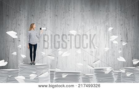 Woman in casual clothing standing among flying paper planes with speaker in hand with grey wall on background. Mixed media.