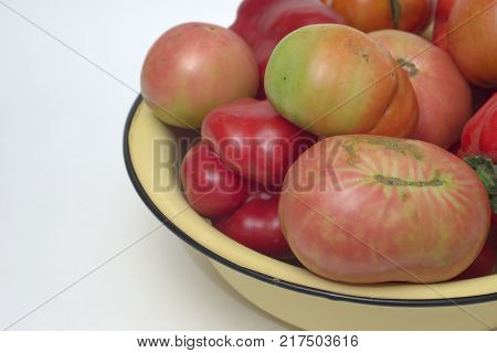 yellow basin with black rim, overfull with red and pink fresh tomatoes and red sweet peppers