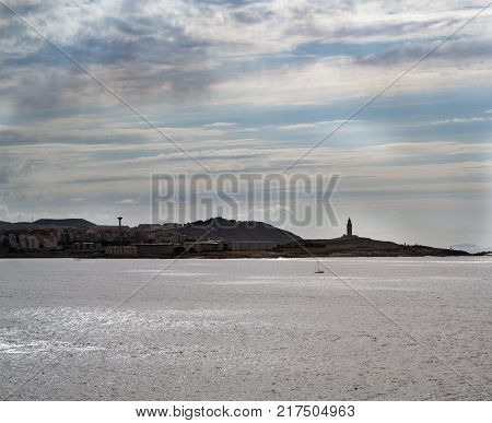 Image of the coast and sky line of La Coruna (Spain) with the tower of Hercules standing out in the right half and cloudy sky with sunbeams reflected in the clouds