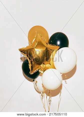 Many colorful round and star helium balloons on white wall background Trendy mockup for design poster, banner etc.