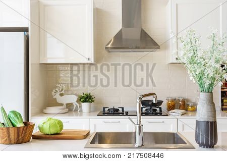 Counter top made in ceramic seen closely with fruits and vegetable on a brown color clay dish next to the modern silver faucet attached to the sink the silver refrigerator .
