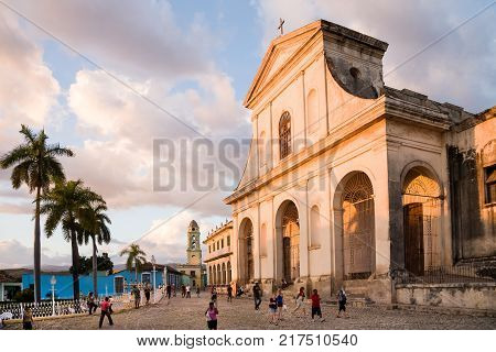 Trinidad Cuba - 2012 December 8 : People walking in front of the colonial Holy Trinity cathedral glowing in the sunset in the main square of Trinidad Cuba