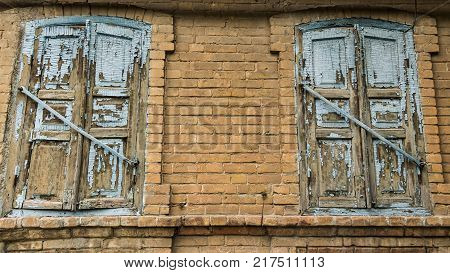 Two old windows closed with blue shutters with peeling paint on a vintage house made of bricks.
