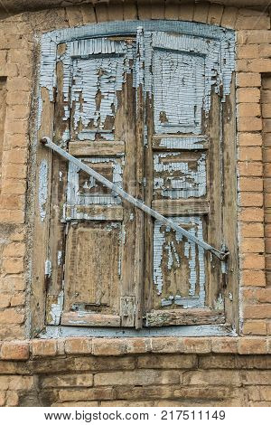 The window is covered with blue shutters with peeling paint on a vintage house made of bricks.