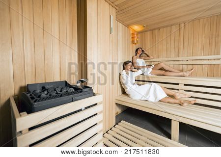 Sauna heater in a cozy sauna and girls relaxing in the background