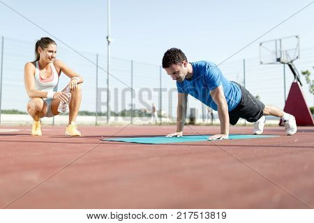Young, beautiful, fit and healthy personal trainer counting push-ups and motivating