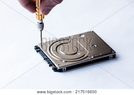 The man's hand turns off the screw on the hard drive using an orange screwdriver.