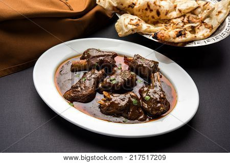 lamb shank or mutton or gosht paya or khur or khoor curry served with indian bread or roti or naan