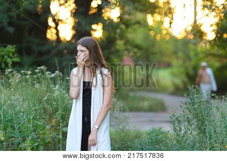 Woman with long hair and beautiful eyes on a green background shows the different human emotions. Lady portrays grief, sorrow, tears, hurt