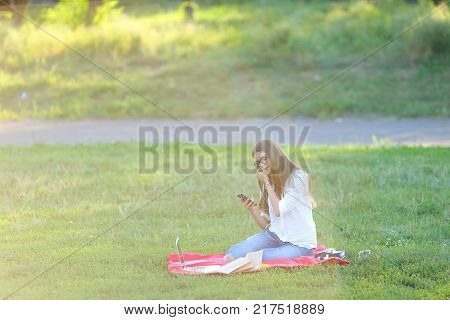 girl listening to music on the nature of the glasses. in the park for a laptop unravels headphones and holding a mobile phone