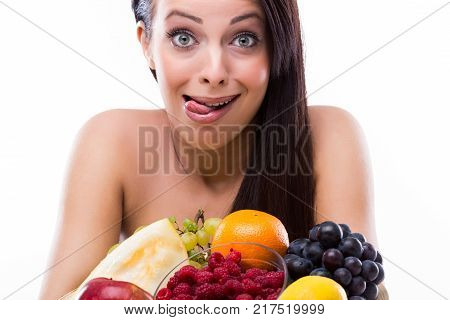 Beautifu youngl woman with fresh fruit and she makes a funny face