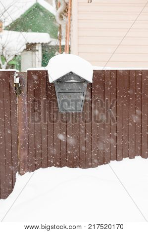 mailbox hanging on a fence by snow in winter