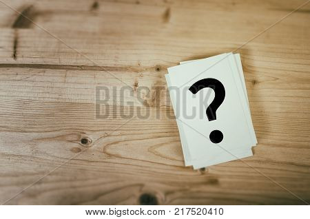 Question mark on wooden desk background. Concept for confusion question or solution.