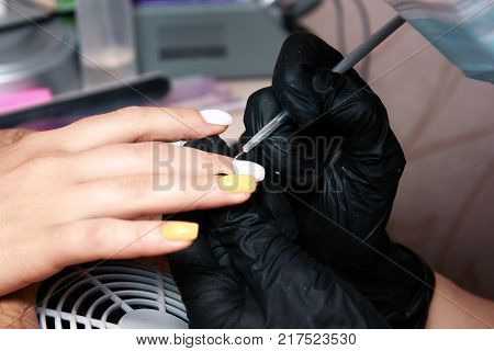 making nail extension, coloring white polish. Covering of enamel on raw nail extension