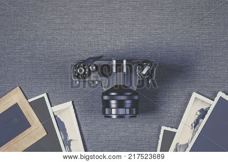 Old black camera and photos with shaped edges. A view from above.