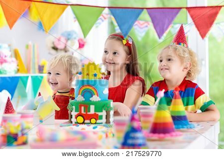 Kids birthday party. Child blowing out candles on colorful cake. Decorated home with rainbow flag banners balloons confetti. Farm and transport theme. Little boy celebrating birthday. Party food.
