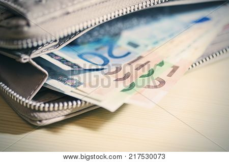 Euro banknotes in wallet. business finance investment saving and cash concept - close up of euro paper money and coins on table