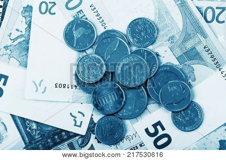 business finance saving and cash concept - close up of euro paper money and coins on table blue colored
