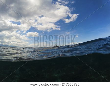 Dark sea water and cloudy blue sky double landscape photo. Tropical seaside banner. Above and below waterline. Natural scene with ocean water surface. Still sea ripples and waves. Distant boat seaview