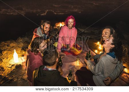 Young hipster friends having fun together at beach camping party by night with campfire light- Friendship travel concept with young people traveler drinking beer at summer surf bonfire -High iso image