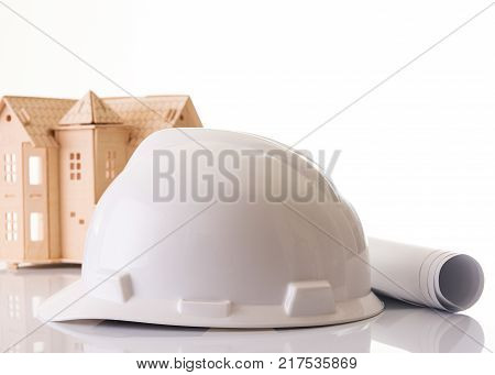 Helmet or hard hat, rolled construction  blueprints, paper clipboard and new house toy model isolated on white background . Architecture and construction concept, close-up