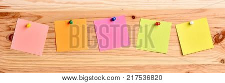 Colorful notes on a wooden board.Texture with notes.A collection of papers for notes.A set of office stickers.Frame for notes.
