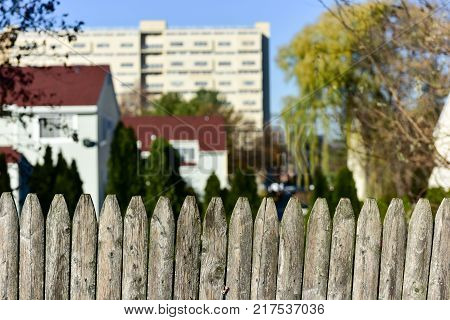 Old wooden picket fence against a city background.