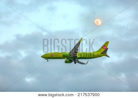Adler, Sochi, Russia - May 2016. An airplane with an open chassis comes on landing in the evening at dusk against a cloudy sky and moon. VQ-BRK S7 - Siberia Airlines Boeing 737-800.