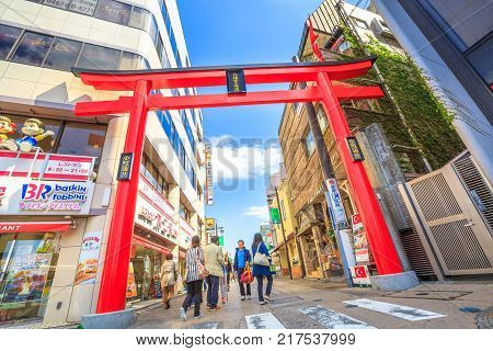 Kamakura, Japan - April 23, 2017: red Torii gate entrance at Komachi-dori Street, the popular touristic shopping street outside Kamakura station in Kamakura center with historic restaurants and stores