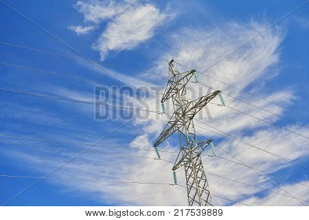View on one outdoor high voltage electric transmission line support metal construction tower pillon on blue cloudy sky. Metal electricity pylon. Industrial background Power transmission tower industry