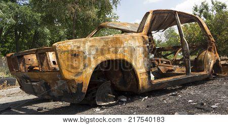 An abandoned, stolen burnt out car close up