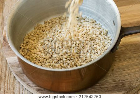 Pouring Whole Grain Brown Rice into Copper Pot Wood Table Motion Rustic Kitchen Interior Healthy Diet Fiber Source Mediterranean Cuisine Close Up