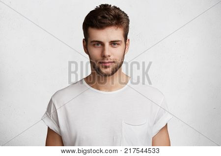 Serious Confident Young Male Student Comes Home After Classes, Dressed Casually In White T Shirt, Wa