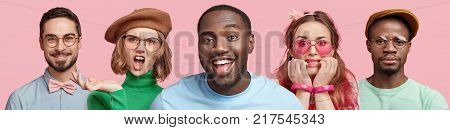 Horizontal portrait of five people express different emotions stand in row next to each other isolated over pink background. Dark skinned smiling male in centre and his friends or relatives